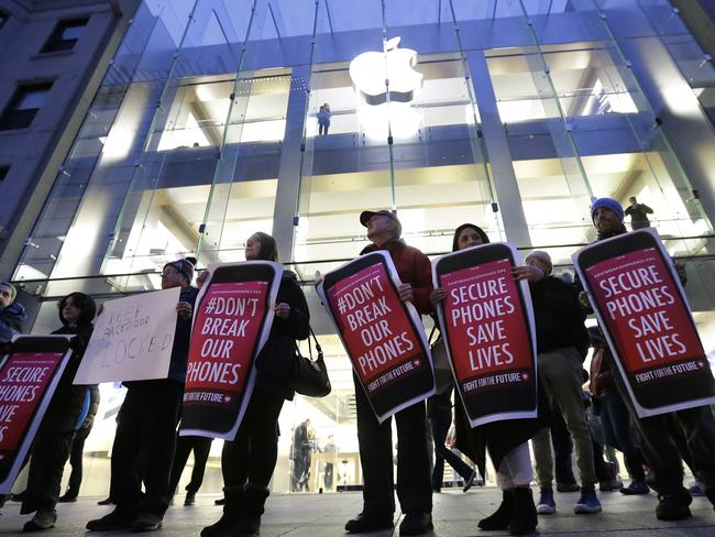 Civil liberties protesters carry placards outside an Apple store in Boston. Picture: AP Photo/Steven Senne