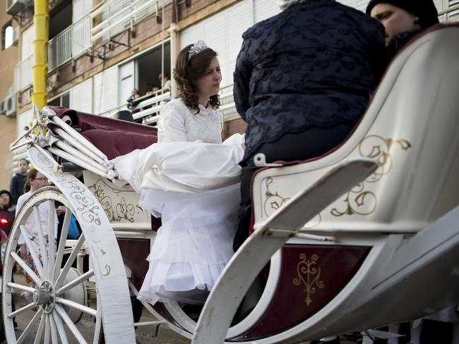 The bride arrives with family members. Picture: AP Photo/Oded Balilty