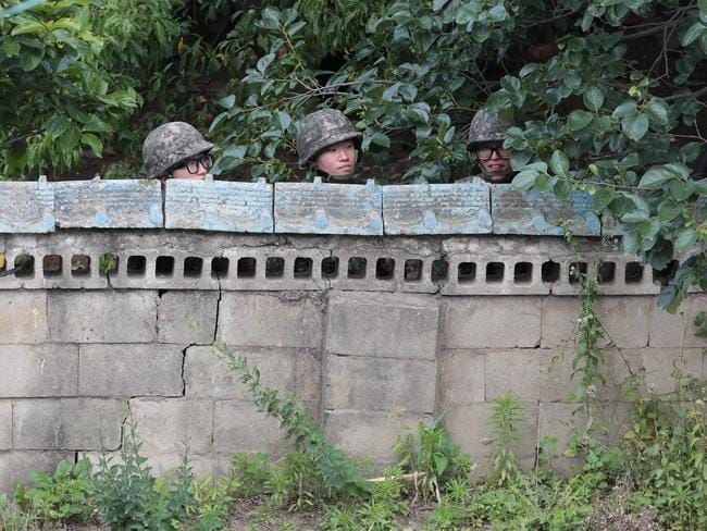 Rampage...South Korean army soldiers hide behind a wall of a private house during a gunfight with a South Korean soldier who is on the run. Picture: AP
