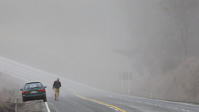 A motorist is surrounded by a cloud of ash on state highway one. Picture: Hagen Hopkins