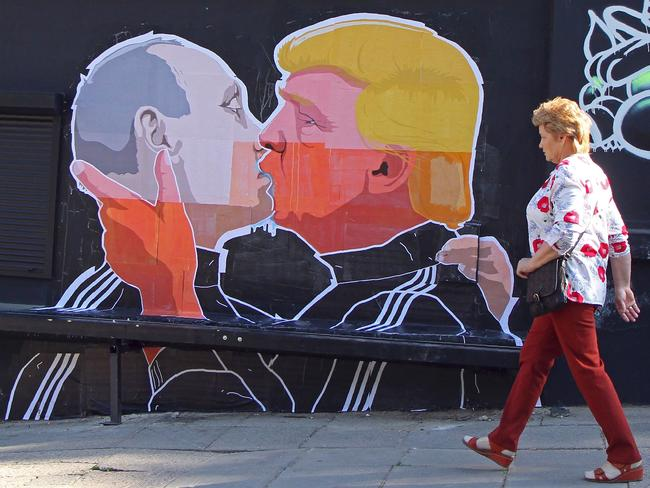 A woman walks past a mural on a restaurant wall depicting US Presidential hopeful Donald Trump and Russian President Vladimir Putin greeting each other with a kiss in the Lithuanian capital Vilnius on May 13, 2016. Picture: Petras Malukas/AFP