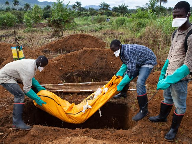 Volunteers in protective suits bury the body of a person who died from Ebola in Sierra Leone.