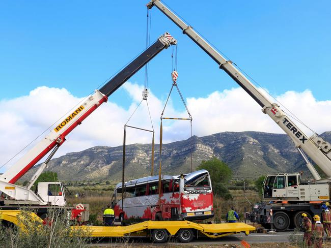 Rescue mission ... two cranes hoist a bus onto a trailer on the Spanish AP7 motorway. Picture: AFP/Pau Barrena