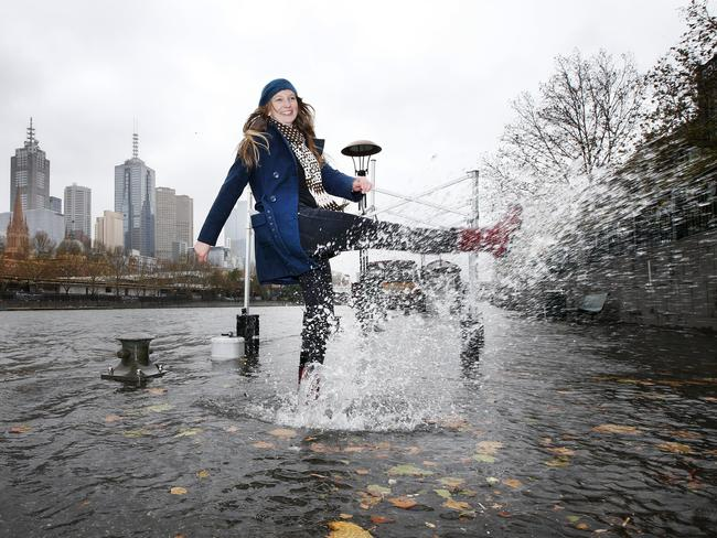 Tara Demarest makes the best of a wet situation as the Yarra River bursts its banks in Melbourne. Picture: David Caird