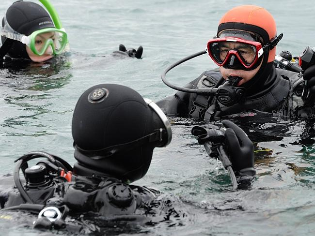On a mission ... Yasuo Takamatsu (right) listens to his instructor in the ice-cold sea water in Onagawa. Picture: Toru Tamanaka