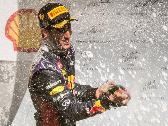 Ricciardo sprays champagne as he stands on the podium after winning the Belgian GP.