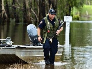 Armed police search the water's edge. Picture: MICHAEL FRANCHI