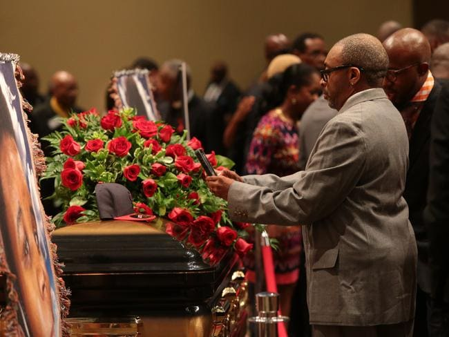 Big names gather ... director Spike Lee takes a picture of a black St Louis Cardinals baseball cap on top of Michael Brown's casket.