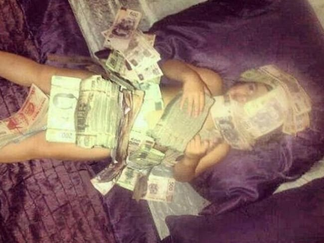 Felix also posts pictures of her children, including this now deleted snap of her son covered in stacks of bank notes. Picture: Twitter