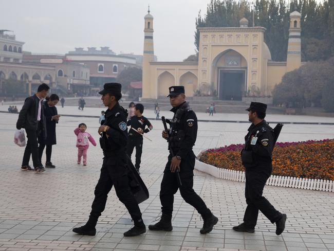 Uighur security personnel patrol near the Id Kah Mosque in Kashgar in western China's Xinjiang region. Authorities are using detentions in political indoctrination centres and data-driven surveillance to impose a digital police state in the region. Picture: Ng Han Guan