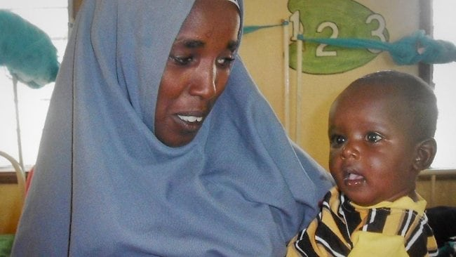 Minhaj Gedi Farah with his mother Assiyah in October, when he was being nursed back to health at the Dadaab refuge camp in Kenya. Picture: AP