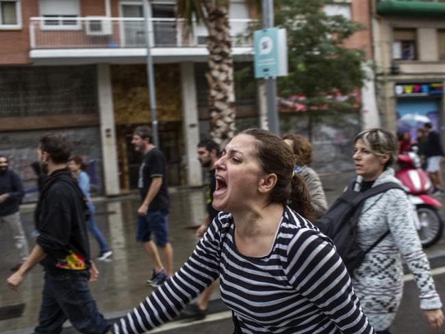 A woman shouts during clashes with Spanish police officers outside the Ramon Llull polling station in Barcelona. Picture: AFP/Fabio Bucciarelli
