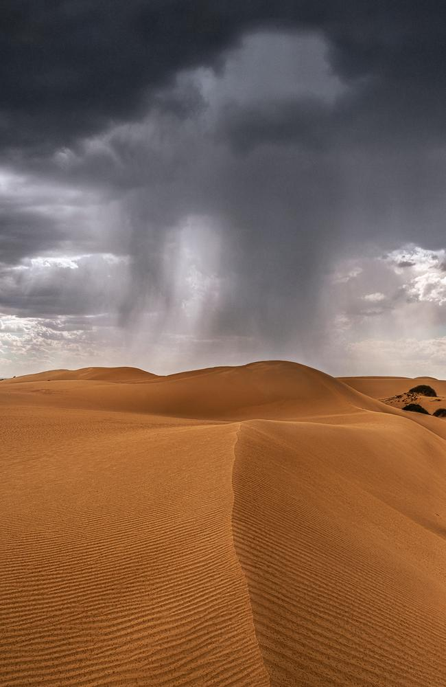 Staggering ... Rain over sand dunes, near Mungo, NSW. Picture: Tony Middleton