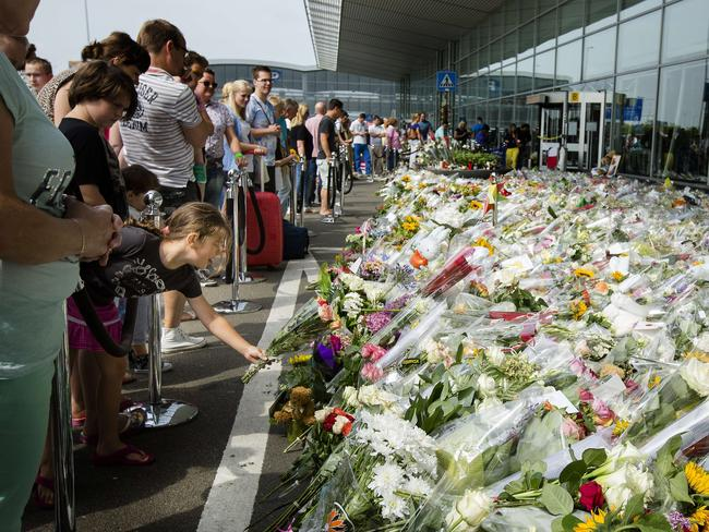 Travellers look at flowers placed in memory of the victims of MH17.