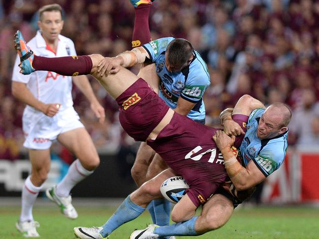 Brent Tate of the Maroons is picked up in the tackle by Josh Reynolds and Beau Scott during the Origin opener. Photo: Bradley Kanaris/Getty Images