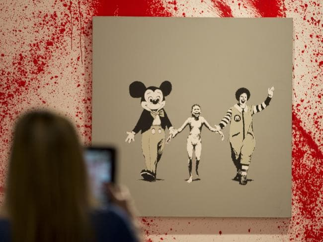 Street art ... a member of the media takes a photo of an art work by British artist Banksy during a press preview of an unauthorised retrospective exhibition showcasing 70 of his artworks. Picture: AP
