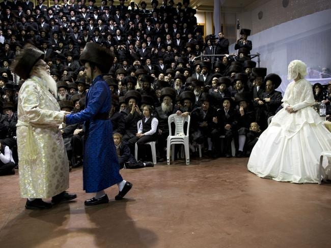 Family members and honoured rabbis dance in front of the bride and dance with the groom. Picture: AP Photo/Oded Balilty