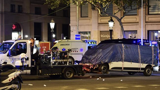 The van which ploughed into the crowd, killing at least 13 people and injuring around 100 others is towed away from the Rambla in Barcelona on August 18, 2017. Picture: AFP / Javier Soriano.