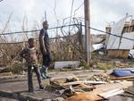 People look at damage on September 7, 2017, in Marigot, near the Bay of Nettle, on the island of Saint-Martin in the northeast Caribbean, after the passage of Hurricane Irma. France, the Netherlands and Britain on September 7 sent water, emergency rations and rescue teams to their stricken territories in the Caribbean hit by Hurricane Irma, which has killed at least 10 people. The worst-affected island so far is Saint Martin, which is divided between the Netherlands and France, where eight of the 10 confirmed deaths took place. / AFP PHOTO / Lionel CHAMOISEAU