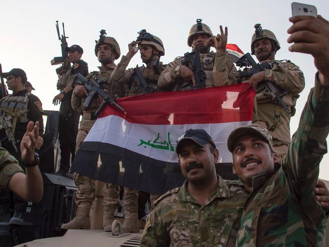 Members of the Iraqi army pose for a selfie during their victory celebrations after a long and bloody fight. Picture: AFP PHOTO / FADEL SENNA