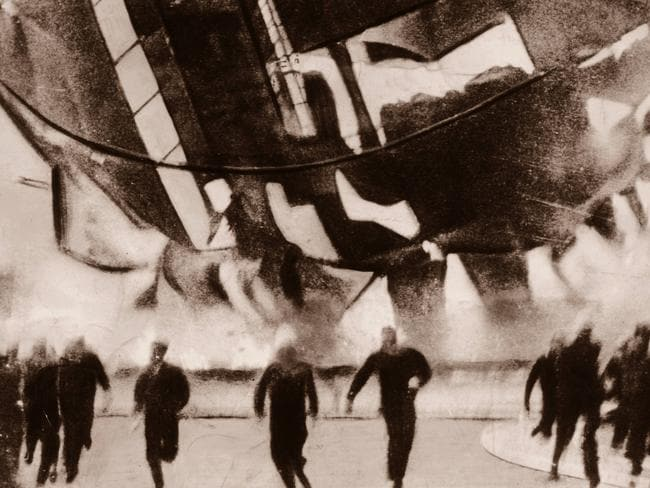 Fifteen storeys tall ... navy crewmen are seen running from the crashing Zeppelin in 1937.