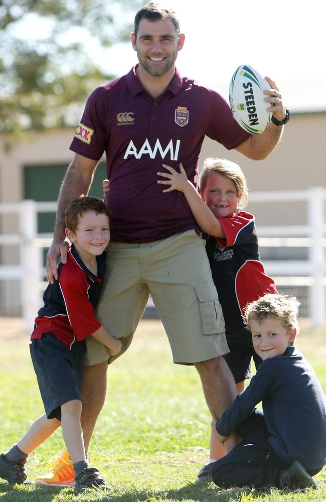 Cam Smith gets tackled by local kids Kai Slade (6), Riordann Heslin (6) and Sienna Neuendorf from Our Lady's Primary School in Longreach.
