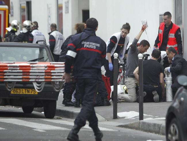 One of the injured is treated outside the offices of the French satirical newspaper.
