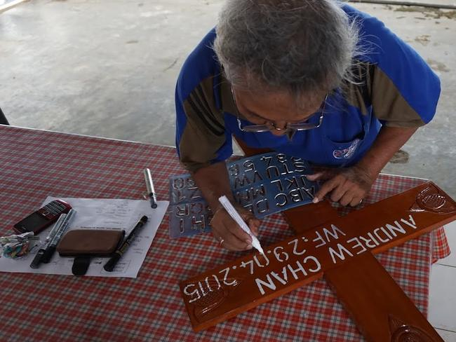 Preparation ... Mortician B. Suhendroputro has been stencilling crosses with the names of victims to be shot by firing squad. Picture: Supplied
