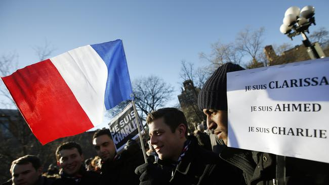 New Yorkers wave a French flag as several hundred people gather in solidarity with the Paris victim in New York's Washington Square Park. Picture: AP