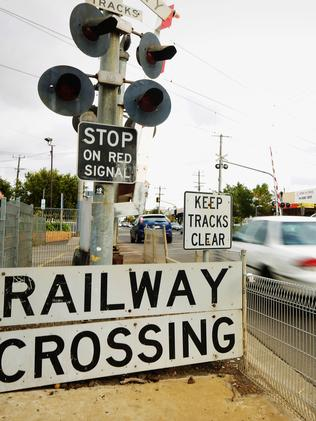 Cars crossing the train line at a level crossing. Picture: Hamish Blair