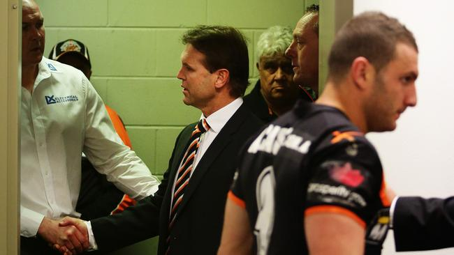 Wests Tigers coach Mick Potter enters the press conference room with Robbie Farah.