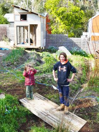 The boys standing next to the backyard veggie patch.