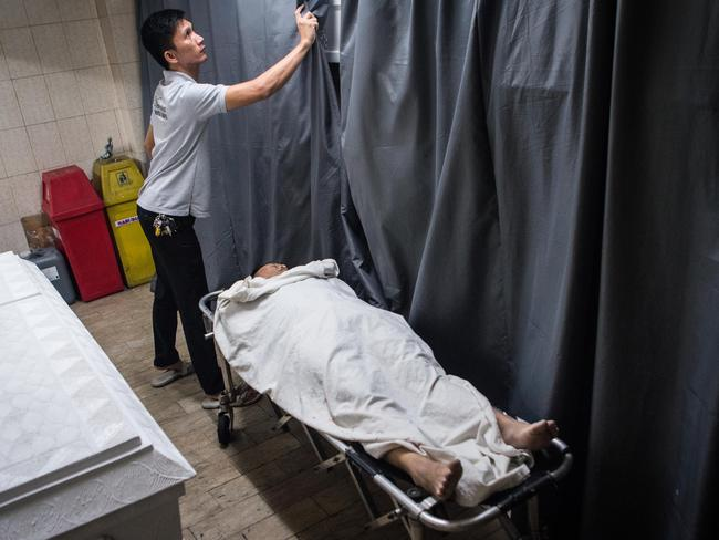 Funeral workers transport bodies of alleged drug dealers and victims of summary executions inside a Manila funeral parlour. Picture: Getty Images