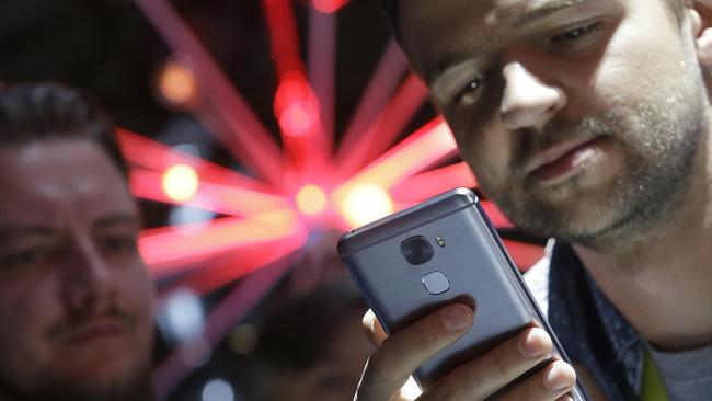 Two men look at a LePro 3 phone. Picture: Jeff Chiu/AP