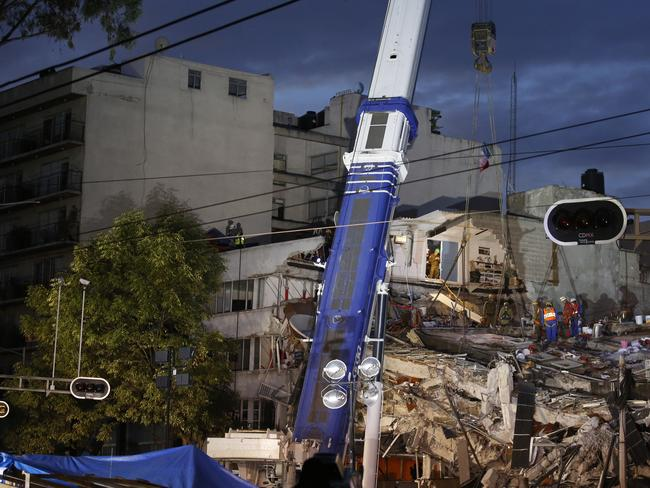Israeli and Mexican rescue workers use a crane to lift a section of the building as rescue workers race against the clock to reach possible survivors trapped inside an office building in the Roma Norte neighbourhood of Mexico City. Picture: AP
