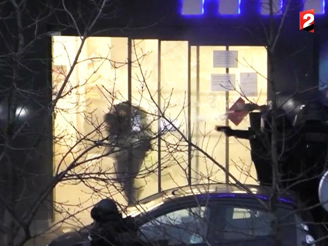 Moved in ... Police storm the supermarket where hostages were being held by terrorist Amedy Coulibaly. Picture: France 2