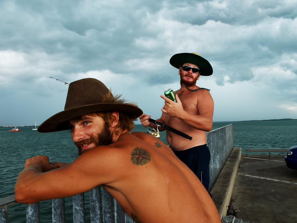 Dylan Rae and James 'Jimbo' Mckenzie fish off Stokes Hill Wharf as storm clouds roll over East Arm towards Darwin city. Picture: Elise Derwin
