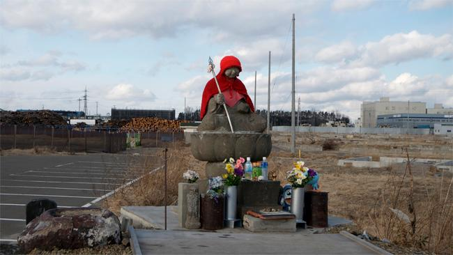 The stone statue - a guardian to children, pregnant women and travelers - sits outside a destroyed school. Picture: Helen Davidson
