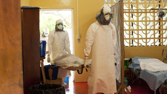 Deadly ... two workers carry the body of an Ebola victim from an isolation ward at a mission hospital outside Monrovia, Liberia.