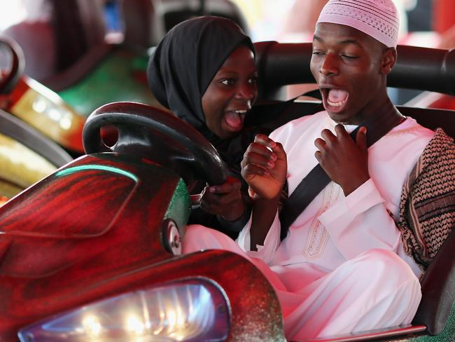 Light hearts ... people ride on bumper cars during an Eid celebration in Burgess Park in London. Picture: Dan Kitwood