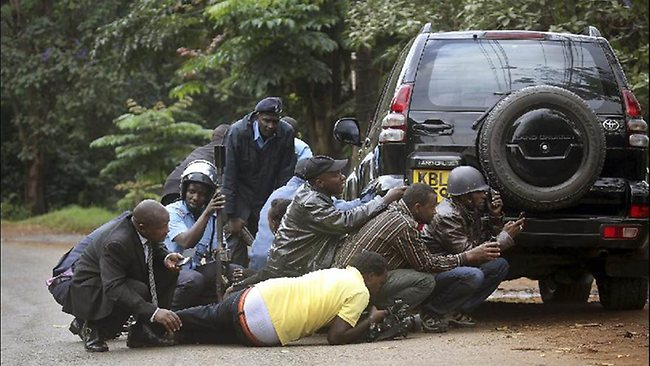 Kenyan security personnel and journalists duck behind a vehicle as heavy gunfire erupts from the Westgate Mall in Nairobi