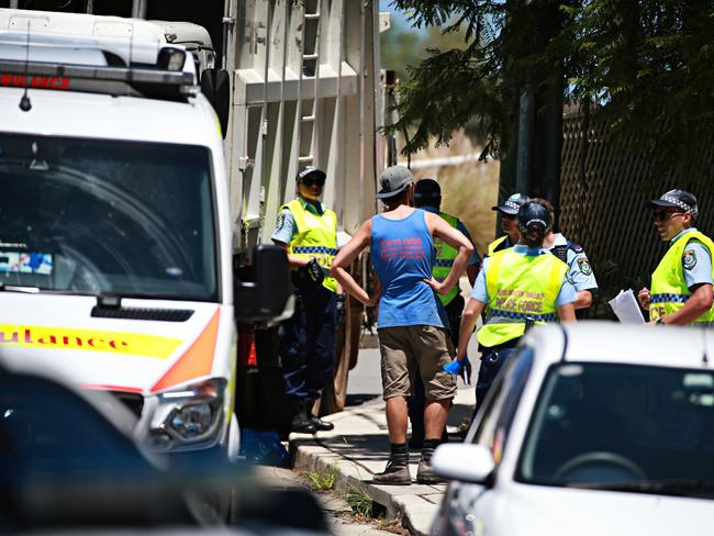 Police with the father of the boy with garbage truck at the scene. Picture: Adam Yip
