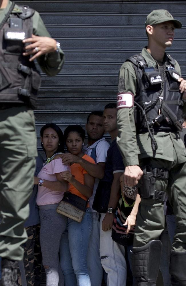 Locals are surrounded by Venezuelan Bolivarian National Guards officers as they line up outside of a supermarket to buy food in Caracas, Venezuela. Protests and looting in western Venezuela over food shortages has left at least seven people dead and many more injured. Picture: AP/Fernando Llano