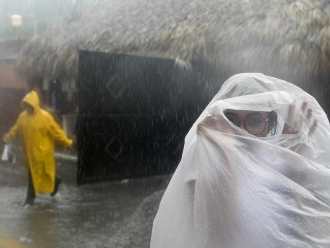 A woman covers herself with a plastic bag as she makes her way to work as Hurricane Maria approaches the coast of Bavaro, Dominican Republic. Picture: AP
