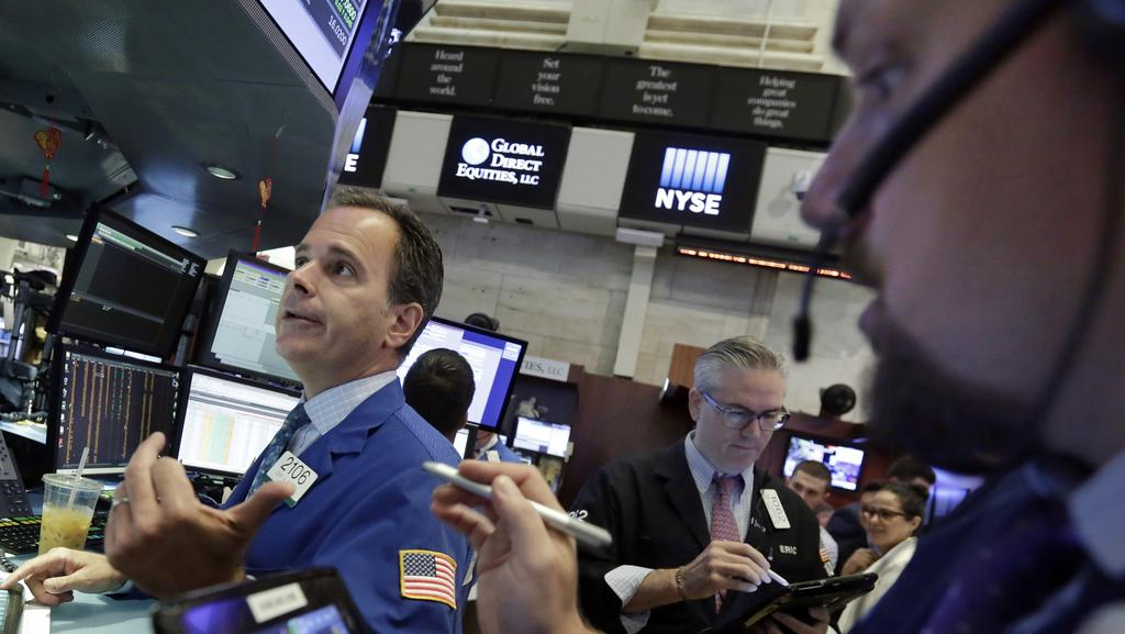 Specialist John Alatzas, left, and traders Eric Schumacher, centre, and Michael Milano work on the floor of the New York Stock Exchange, Monday, July 17, 2017. Picture: Richard Drew/AP