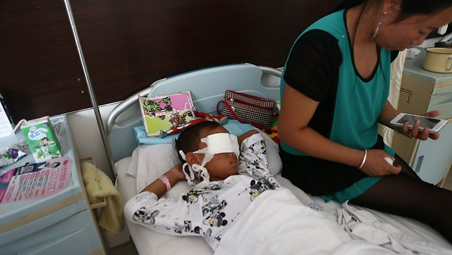 A boy (L) lies on his hospital bed with his eyes covered with bandages as his mother sits next to him at a hospital in Taiyuan, north China's Shanxi province on August 27. The six-year-old boy from northern China was drugged and had his eyes gauged out, reports said, in a gruesome attack that may have been carried out by a ruthless female organ trafficker. CHINA OUT AFP PHOTO