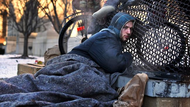 Nicholas Simmons warms himself on a steam grate during freezing temperatures in Washington. He was later reunited with his ...
