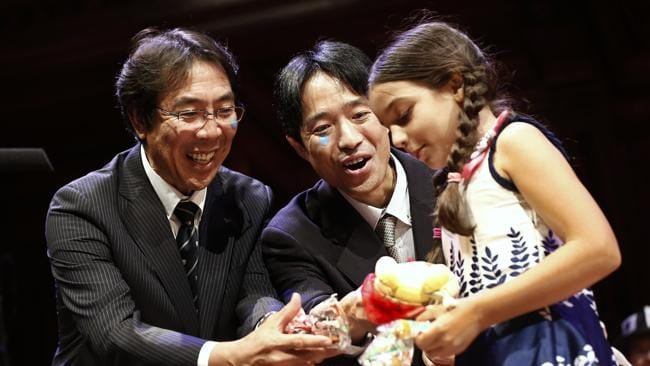 """After accepting the Chemistry Prize during the annual Ig Nobel prize ceremony at Harvard University, Nobuaki, left, and Muneaki Tomotake, both of Japan, give gifts to """"Miss Sweetie Poo,"""" who tried to get them to end their acceptance speech. (AP Photo/Winslow Townson)"""