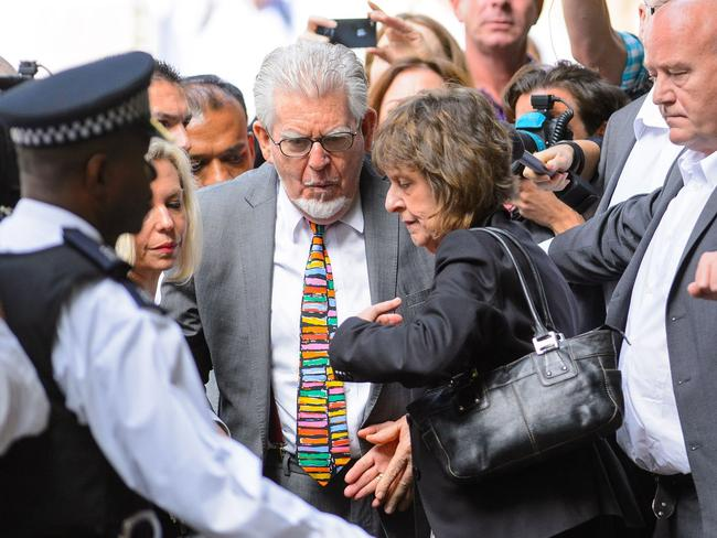 Last walk of freedom ... Rolf Harris, centre, accompanied by his daughter Bindi, background left and niece Jenny, centre right, arrives at Southwark Crown Court to be sentenced. Picture: Dominic Lipinski