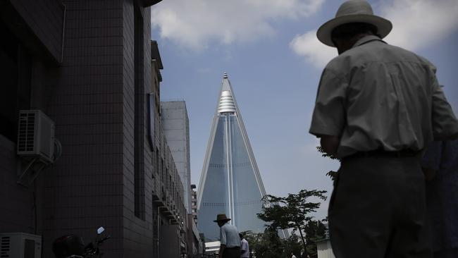 Elderly North Korean men walk on a sidewalk with the 105-story pyramid-shaped Ryugyong Hotel, which has been under construction since 1987, seen in the background in Pyongyang.